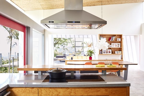 A look inside at the kitchen and dining area, which is open to the outdoors and occupies one of two structures connected by a bridge. The space is outfitted with a Whirlpool glass cooktop and an AKDY hood.