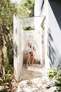 "The girls rinse off in the partially enclosed shower outside the master bathroom. ""The kids really love the ups and downs and ins and outs of the house,"" says Daniela."