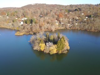 The .66-acre Willow Island sits just off shore in the middle of Putnam Lake in Patterson, a historic town right on the border of New York and Connecticut.