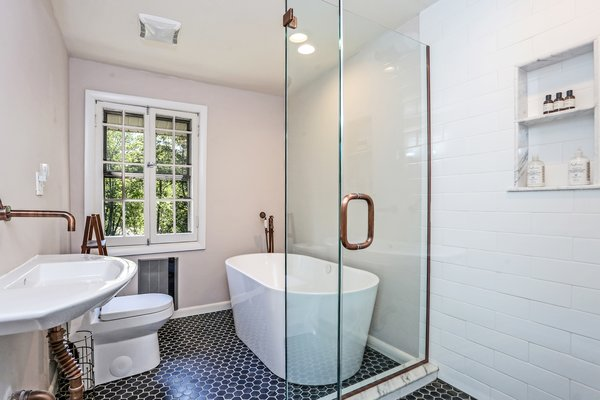 The only full bathroom is also located upstairs. A complete renovation included new tile, a stand-alone soaking tub, and a walk-in shower.