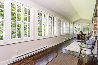 A line of windows wraps around the sunroom, framing views from multiple sides of the property.