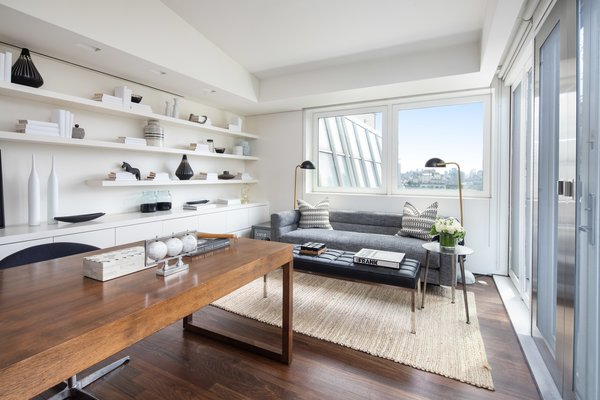 A small office is located off the kitchen, complete with built in cabinetry and shelving. The nook is made bright and airy from the large doors and east-facing window.