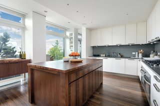An Italian-designed kitchen is discretely hidden behind the dining area. Outfitted for entertaining, a large butcher block island sits in the middle of the space, surrounded by two ovens, a Miele six-burner cooktop, and a Sub-Zero refrigerator. There is also direct access to an outdoor kitchen with built-in grill and preparation area.