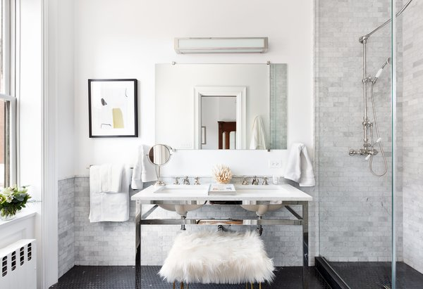 The windowed master bath features Nero Marquina marble flooring, Carrara marble dual sinks, and a glass standing shower. The bath fixtures are nickel plated.