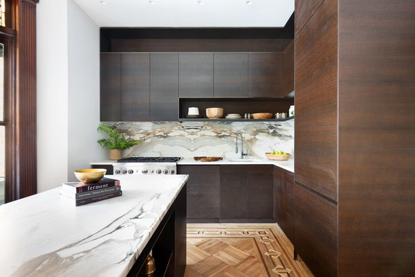 Located at the back of the home, an updated kitchen offers modern cabinetry finished in dark, fumed oak with patinated brass inlay. Contrasting with the wood tones is Calacutta Paonazzo marble along the countertops and backsplash.