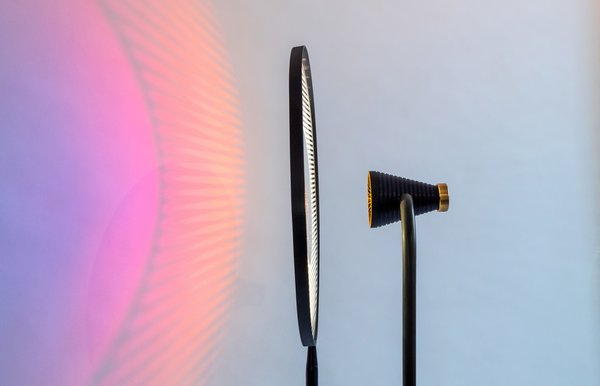 The Raa lamp shines through an engraved acrylic shade' which creates shadows and textured patterns on the wall.