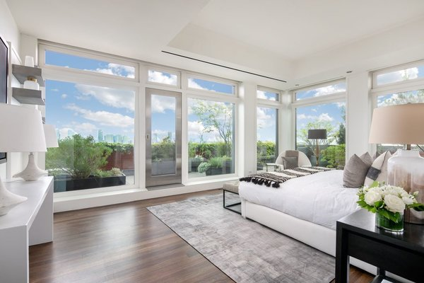 In an opposite corner of the apartment, the master suite offers floor-to-ceiling windows along two sides, as well as direct access to a private section of the terrace. The bright space also includes not one but two full bathrooms.