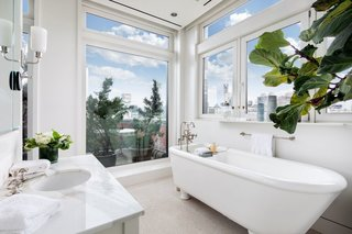 A look at one of two master bathrooms, this one with a large soaking tub. Windows flood the space in natural light and offer iconic views of Midtown Manhattan.