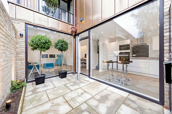 Crossing the threshold from the street, residents and guests enter the property via a spacious private courtyard with floor to ceiling glass offering a peek to the inside.