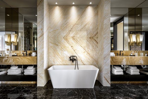 The Bisha Suite bathroom features a large shower, tub, and two vanities—all wrapped in golden spider marble.