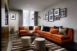 A velvet, orange sectional pairs with a plush, handwoven rug in the 900-square-foot Alexander Suite, which also features black oak and a grand terrace.