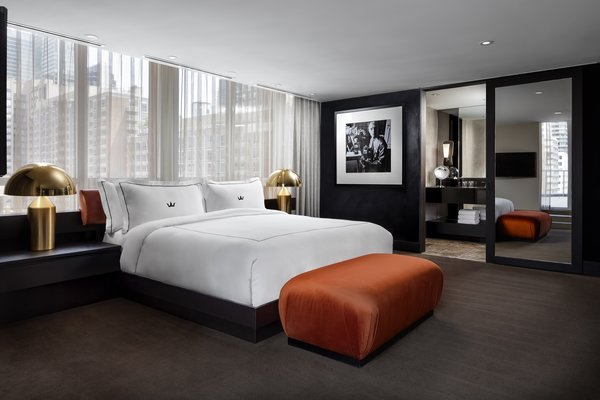 Brass, orange, and deep brown tones continue in the bedroom.