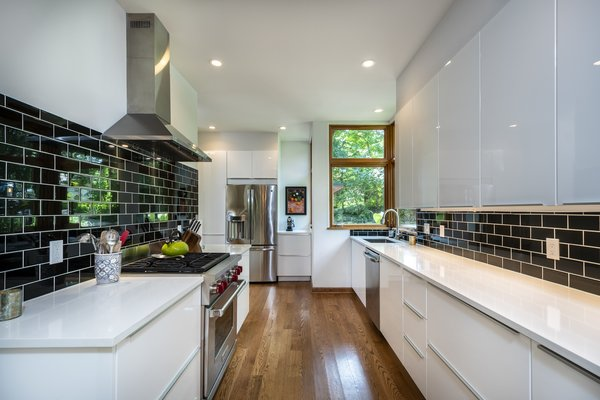 The large galley kitchen was completely modernized as part of the renovation. The long space leads to a large corner window in front of the sink, which allows warm natural light inside.