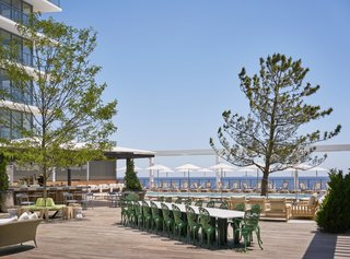The pool deck is paved with Ipe wood and punctuated with black pine evergreens and honey locust trees. The concrete-topped communal table was made in Italy. Surrounding it are aluminum chairs inspired by the classic Victorian garden chair—a nod to Asbury's Victorian-era beginnings.