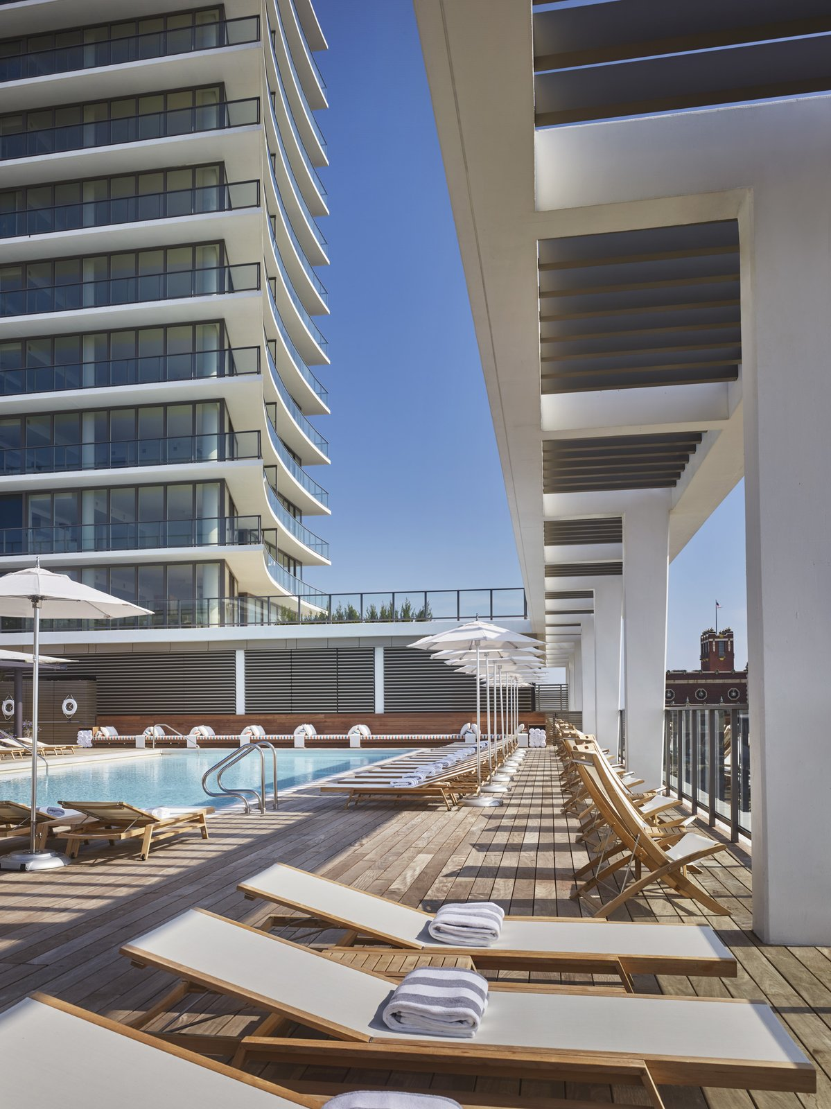 Outdoor, Large Patio, Porch, Deck, Swimming Pools, Tubs, Shower, Large Pools, Tubs, Shower, and Wood Patio, Porch, Deck Teak lounges and chairs surround the pool area, which overlooks the ocean. The residential tower is visible in the background.  Asbury Ocean Club Hotel from A New Five-Star Hotel Gives the Jersey Shore an Upgrade