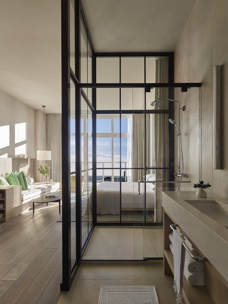 The showers are enclosed in glass to bring in natural light and give the feeling of showering outdoors. But not to worry—there are drapes for privacy when needed.