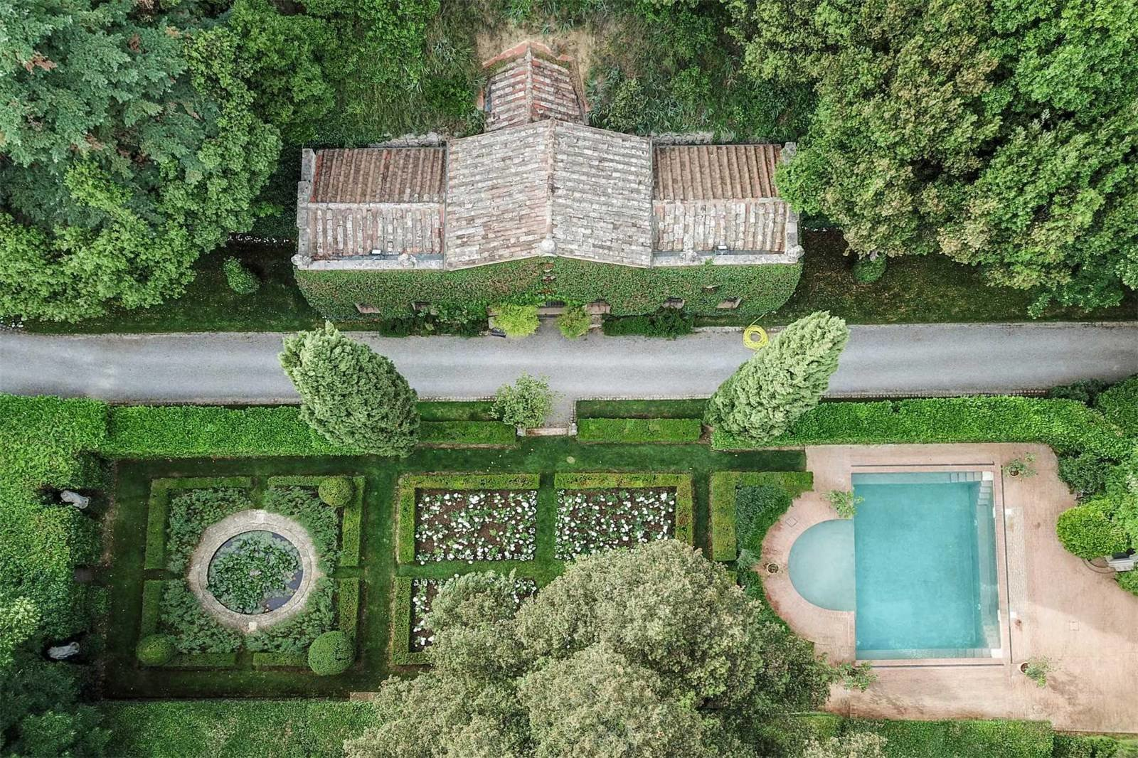 An aerial view of the pool and rose garden. Here, you can also see part of the shady fitness track, formed from tree-lined avenues circling the home.  Photo 13 of 13 in Peek Inside Valentino's Ornate Tuscan Villa, Listed For $13.2M