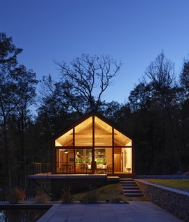 Like a lantern in the night, the cabin glows in its wooden setting once the sun goes down.