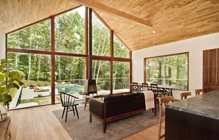 Floor-to-ceiling windows span the entire width of the living room, illuminating the space with natural light. A sliding door provides access to the wraparound porch and pool in the backyard.
