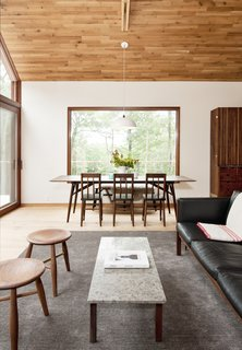 The home provides an idyllic space for entertaining, with the living and dining areas offering framed views of the surrounding nature through large-scale picture windows and slider doors.