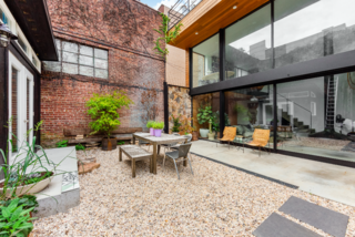 The backyard garden is an oasis from city life, with room for plenty of outdoor seating. Mossman also revived a small, detached studio off to the left.