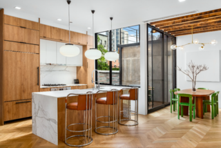 The kitchen is grounded by a Carrera marble island, over which hangs a set of opaline pendant lamps from the 1970s. The bar stools are also vintage from the 1970s, while the bright green chairs around the dining table are by Bruno Rey.