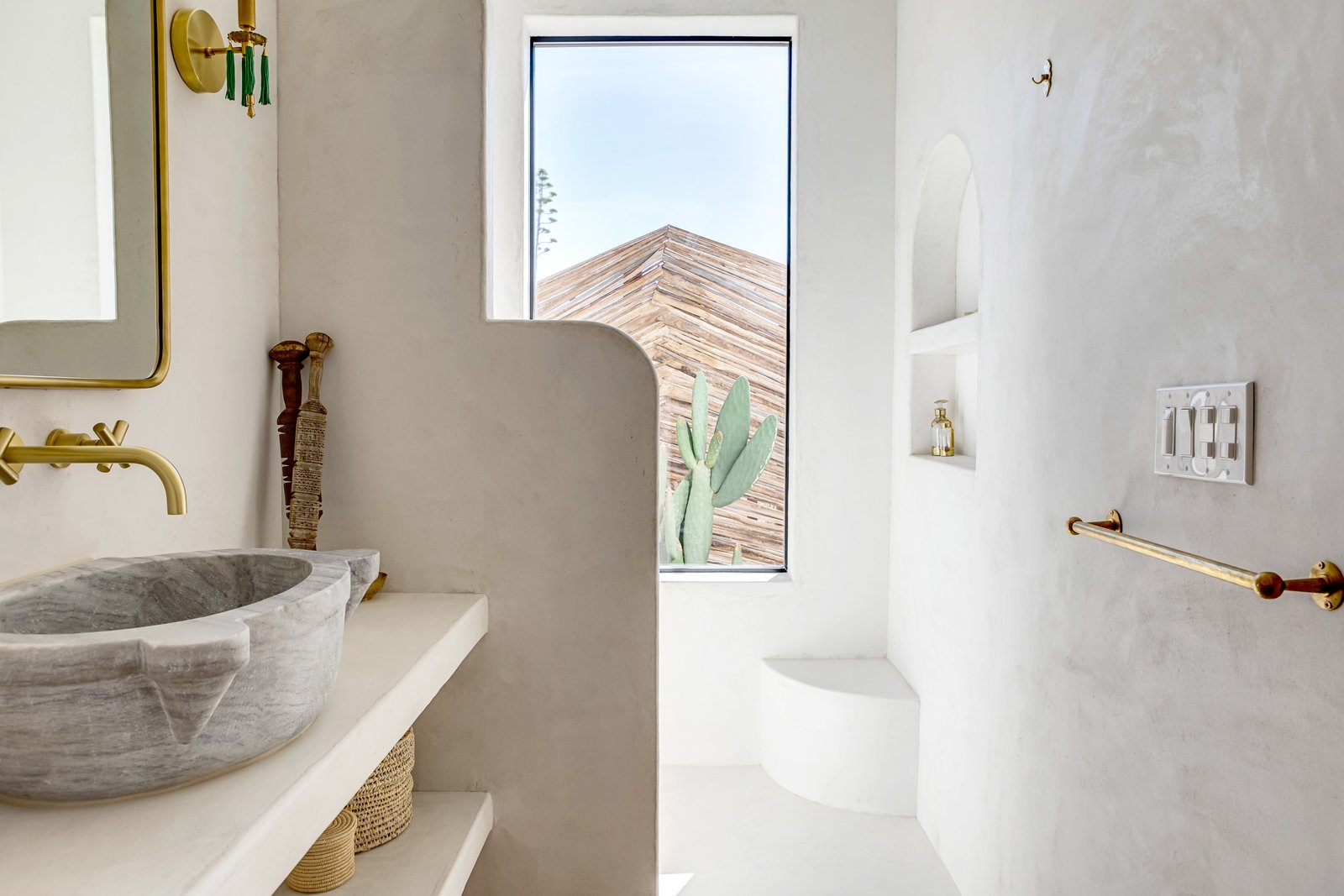In the en-suite bathroom of a California vacation home, the walls and the shower are coated in tadelakt, reflecting the owners' inspiration from the local landscape and travels abroad.  Photo 4 of 7 in 7 Moroccan-Style Spaces With Tadelakt Accents from Construction Diary: A Couple Build a Moroccan-Inspired Retreat in Joshua Tree
