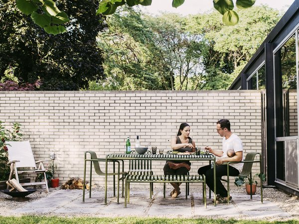 Brooke and Kyle Hoff in their patio garden. The table and chairs are from the Hay Palissade collection, and the rocker is by Kingsley Bate.