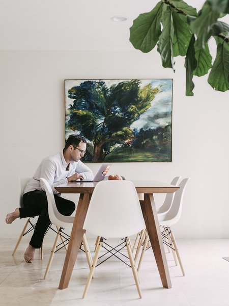 Hoff at work. The dining area features a table by Gus* modern and Eames moulded plastic chairs. The painting is by Simon Gaon.