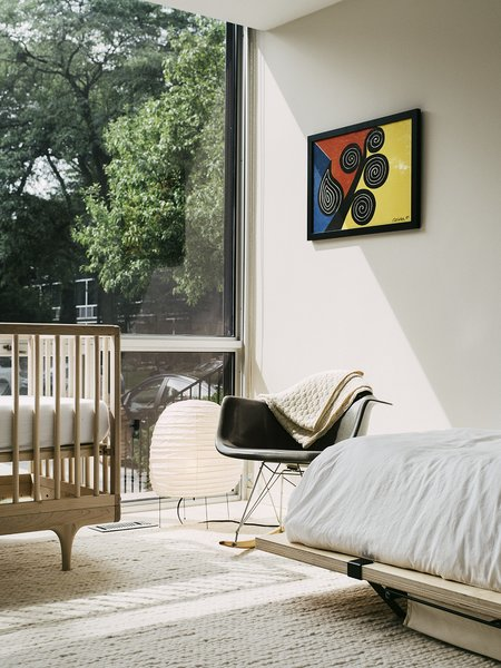An Eames rocker and a Noguchi lamp round out the cozy, daylit bedroom.
