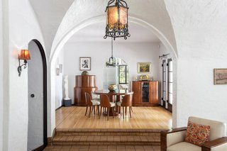 Groin vaults and barrel ceilings can be found all throughout the home, connecting one living space with another. Here, the living room steps up into the bright dining area.