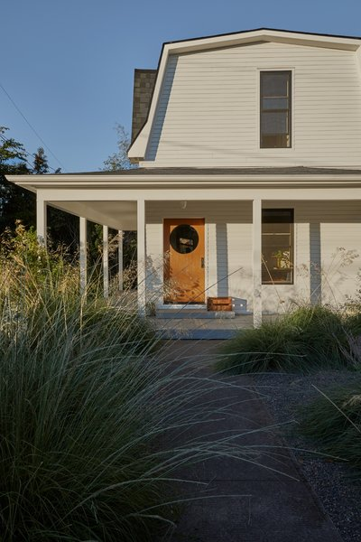 A full exterior remodel of the older house allowed Cornuelle and Tall Firs to match its siding and trim to the new ADU. They designed a front door with a circular cut-out, bringing a modern touch to the traditional entry.