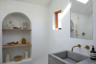 The bathroom is entirely white cement waterproof plaster with natural concrete on the floor, and a hand-poured concrete sink.
