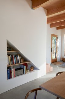 A cut-out, triangular shelf underneath the staircase allows Cornuelle to display art and books.