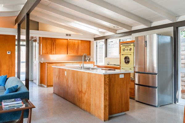 In the kitchen, a new Quartz counter tops the central island. The original cabinetry and pale-yellow Western Holly oven enhance the house's vintage aesthetic, paying homage to the past.