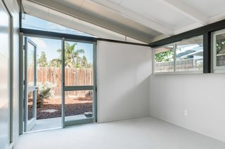 Many of the rooms provide direct access to the backyard area. The vaulted ceiling and expansive windows and doors allow the interiors to feel much larger than its actual size.
