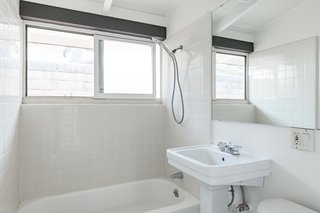 Similar to the rest of the property, the bathroom boasts a clean, crisp white palette, and is well lit thanks to the sliding horizontal window above the shower/tub.