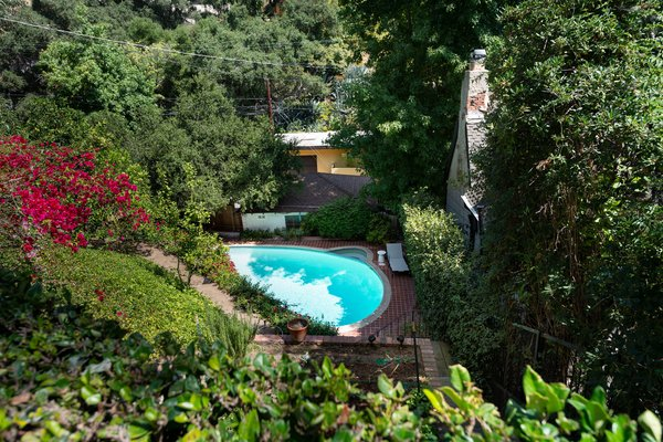A pristine swimming pool awaits further down the sloping grounds, with a pavilion and fire pit just steps away. An abundant vegetable garden is also located on the secluded lot.