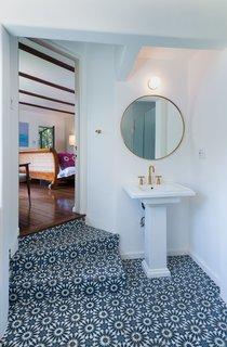 Striking blue tiles line the floors in the adjoining bathroom.