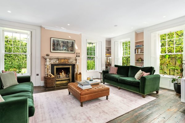 Along the back of the home, an elegantly designed formal living room features large windows along both sides and a marble fireplace.