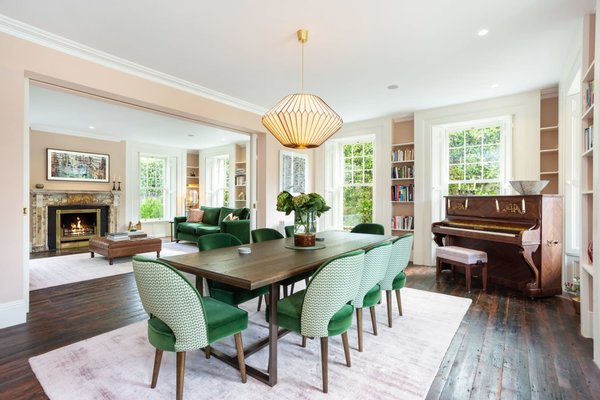 To the right of the main entrance is a formal dining room, which features built-in bookcases and broad panel wood flooring. The floors, which run throughout the rest of the home, were salvaged and refinished on site.