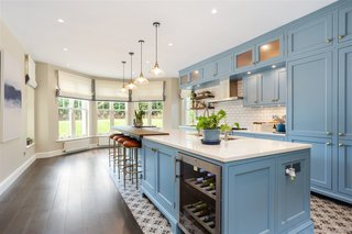 The baby-blue cabinets contrast with a white subway-tiled backsplash and mosaic-tiled flooring. A large bay window overlooks the front driveway and lawn, while allowing tons of natural light into the space.
