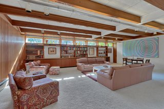 A look at the spacious family room, which features additional built-ins, wooden beams and paneling, as well as clerestory windows that invite long rays of natural light into the space.