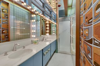 The master suite feels like a throwback to the 1950s. Clerestory windows stretch along the vanity, while bulb lighting and a mirrored ceiling add to the space's retro vibe.