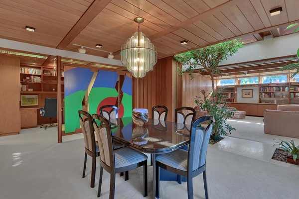The living room also flows into a formal dining room. Wood paneling lines the walls and ceiling, with an abstract screen and indoor plantings dividing the space from a family room and office.