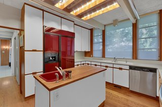 Another view of the kitchen, which offers plenty of cabinetry and countertop space. A central island offers an additional prep area, while large windows provide views of the yard.