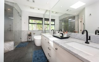 The master bath includes a marble-lined steam shower and vanity, as well as a separate soaking tub.