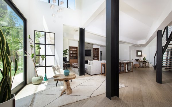 The airy living room—tucked underneath a vaulted ceiling—flows between the kitchen and dining areas. A staircase leads to a voluminous double-height gym.