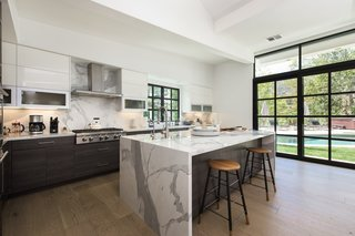 The remodeled kitchen features high-end appliances and a marble-wrapped island.