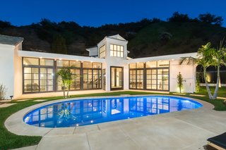 At dusk, the home's interior glows like a lantern against the icy blue pool.